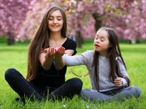 Big sister and little sister sit together on a lawn with cherry blossoms behind them