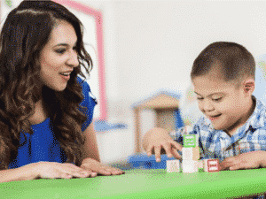 Boy with down syndrome learning with a teacher with blocks