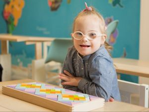 Child with Down syndrome in classroom looking to camera