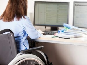 Secondary Transition Preparation - a woman in a wheelchair sits at a desk and works on a desktop computer