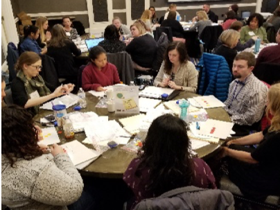 Group of people attending a math workshop around a table