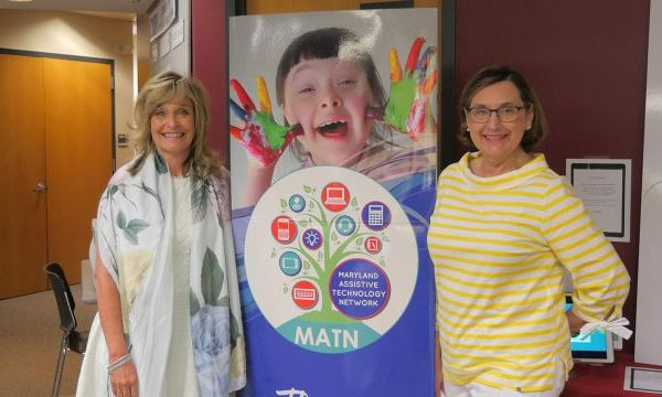 Marcella and Jackie pose in front of an MATN banner