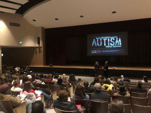 Marcella and Tiffany presenting at the Autism Waiver Services workshop in a large auditorium