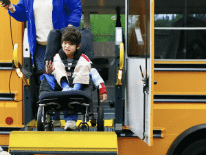 Young boy in wheelchair exiting bus with the help of a ramp