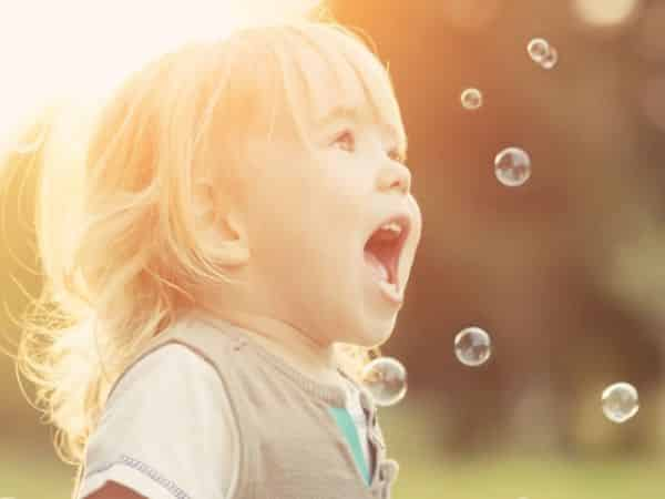 Excited young girl looking at bubbles