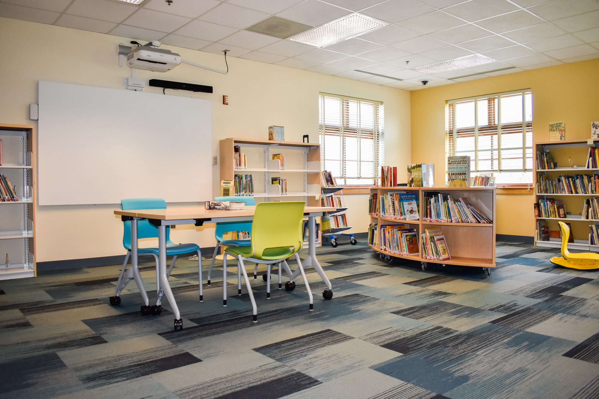Brand new media center with brightly colored walls, rug, chairs, and bookshelves