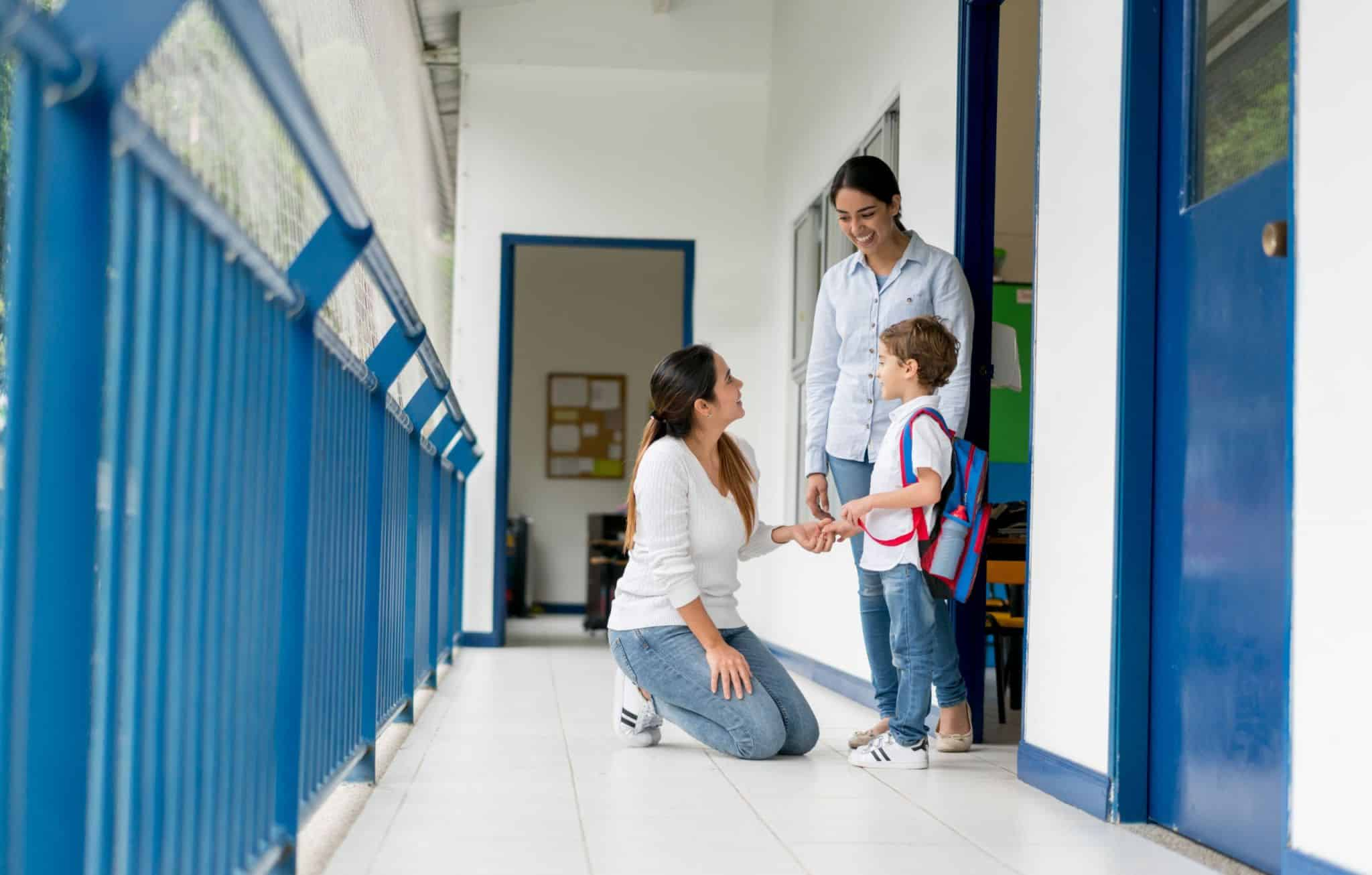 A mother and child welcomed by a teacher outside of a classroom in front of blue lockers