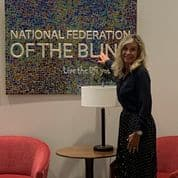 """Marcella stands in front of a tactile sign that reads """"National Federation of the Blind"""""""