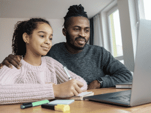 Father helping young student study remotely