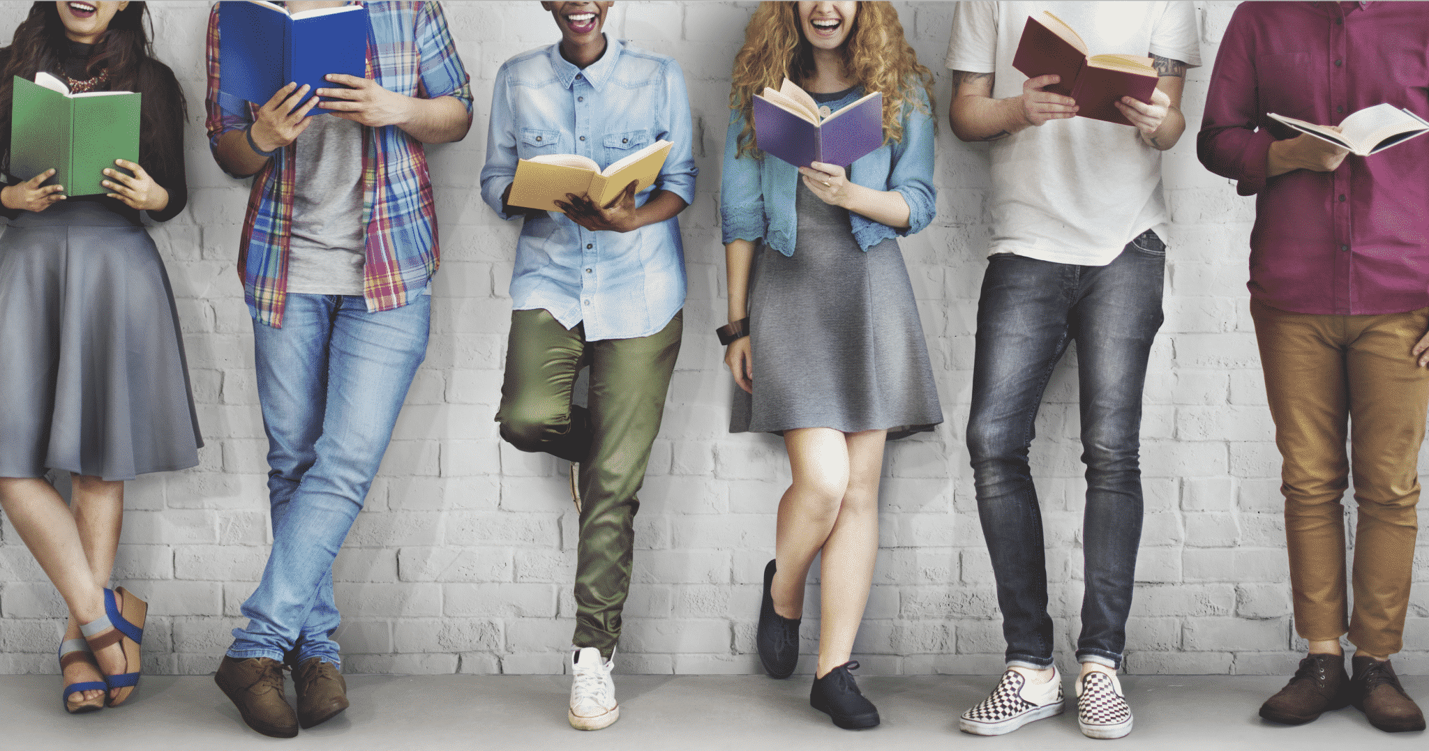 Bunch of students standing against a wall reading